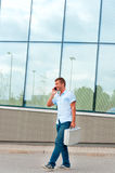 Business man with metal case and mobile phone in front of modern business building Royalty Free Stock Photography