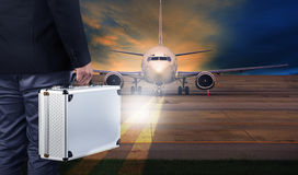 business man with metal strong luggage standing in airport runways and air plane preparing to departure stock photo