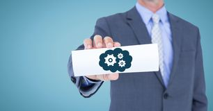 Business man mid section with card showing blue cloud and gear graphic against blue background. Digital composite of Business man mid section with card showing Royalty Free Stock Images