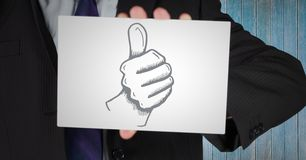 Business man mid section with card showing thumbs up doodle against blue wood panel. Digital composite of Business man mid section with card showing thumbs up Royalty Free Stock Image
