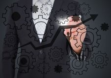 Business man mid section drawing cogs and arrow doodle with flare against grey background. Digital composite of Business man mid section drawing cogs and arrow Royalty Free Stock Photography
