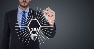 Business man mid section drawing white lightbulb graphic against grey background Stock Images