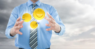 Business man mid section with flares and emojis between hands against cloudy sky Stock Image