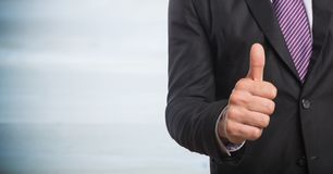 Business man mid section giving thumbs up against blurry grey wood panel Royalty Free Stock Image