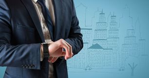 Business man mid section looking at watch against blue background with city doodle Stock Photos