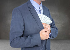 Business man mid section putting money away against grey wall Stock Photos