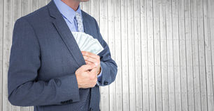 Business man mid section putting money away against grey wood panel Stock Photography