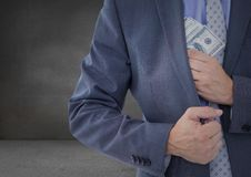 Business man mid section putting money away in grey room Royalty Free Stock Images