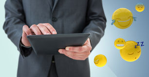 Business man mid section with tablet next to emojis and flare against blue background Stock Photo
