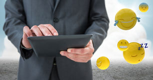 Business man mid section with tablet next to emojis and flare against cloud and ground. Digital composite of Business man mid section with tablet next to emojis Stock Photography