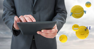 Business man mid section with tablet next to emojis and flare against cloudy sky Royalty Free Stock Photography