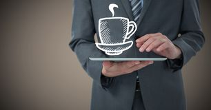 Business man mid section with tablet and white coffee graphic against brown background Stock Photo