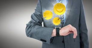 Business man mid section with watch and emojis with flares against grey background. Digital composite of Business man mid section with watch and emojis with Royalty Free Stock Photo
