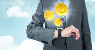 Business man mid section with watch and emojis with flares against sky. Digital composite of Business man mid section with watch and emojis with flares against Royalty Free Stock Photography
