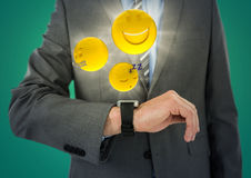 Business man mid section with watch and emojis with flares against teal background. Digital composite of Business man mid section with watch and emojis with Stock Photography