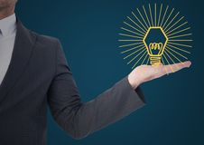 Business man mid section with yellow lightbulb graphic in hand against blue background Royalty Free Stock Photo