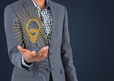 Business man mid section with yellow lightbulb graphic in hand against navy background Royalty Free Stock Images