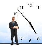 Running out of time business deadline stress. A business man is minutes away from being hanged by a clock with a noose hanging from it that is around the Stock Image