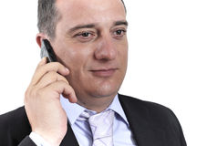 Business man with a mobile phone. On his ear isolated on white Royalty Free Stock Photos