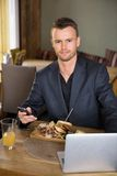 Business man With Mobile phone And Laptop. Portrait of young business man with mobilephone and laptop having meal in restaurant Stock Images