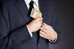 Business man and money. Business man in suit putting banknotes  (fifty euros) in his jacket breast pocket Stock Image
