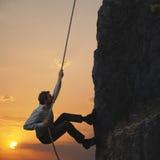Business man and mountain. Business man climbs a mountain Stock Photo
