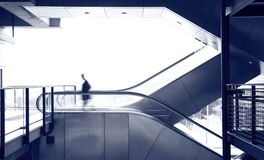 Business man move on escalator. Blue tone Stock Images