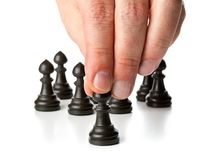 Business man moving chess figure in front of other chess figures. Management, leadership, teamlead or strategy concept over white background Stock Photo