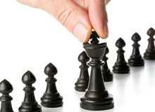 Business man moving chess figure in front of other chess figures. Management, leadership, teamlead or strategy concept over white background royalty free stock photos