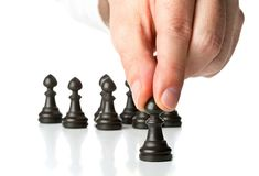 Business man moving chess figure in front of other chess figures. Management, leadership, teamlead or strategy concept over white background Royalty Free Stock Images