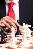 Business man moving his king. On the chessboard Royalty Free Stock Photos