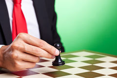 Business man moving a pawn. Over green background Royalty Free Stock Image