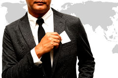 Business man with name card composite with wolrd map. Business man with a name card composite with wolrd map Royalty Free Stock Image