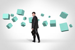 Business man near with turquoise cubes royalty free stock image