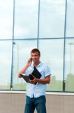Business man with notebook and mobile phone in front of modern business building Stock Images