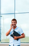 Business man with notebook and mobile phone in front of modern business building Stock Photography