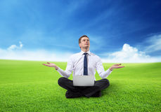 Business man with notebook sitting on grass Royalty Free Stock Photos