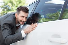 Business man obsessing about cleanliness of car. Car care. Business man obsessing about cleanliness of his new car royalty free stock photo