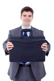 Business man offering a black briefcase Royalty Free Stock Photos