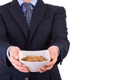 Businessman offering a cereal bowl. Stock Photos