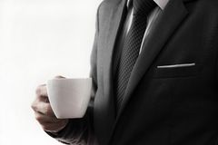 Business man offering cup of coffee. Isolated on white Stock Photo
