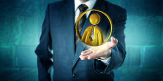 Business Man Offering A Golden Office Worker Icon. Business man offering a golden office worker symbol hovering above the open palm of his left hand. Business Stock Photography