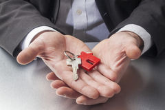 Business man offering you new home key Royalty Free Stock Photo