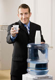 Business man offers camera glass of water Royalty Free Stock Image