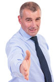 Business man offers a handshake and smiles Stock Photos