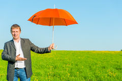 Business man offers a sun umbrella Stock Photos