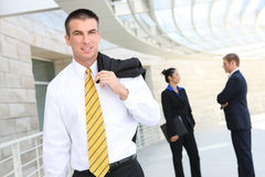 Business Man at Office. Handsome business man at the office with workers in background Royalty Free Stock Photo