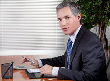 Business Man in Office. A handsome business man looks up from his work while at desk Royalty Free Stock Image