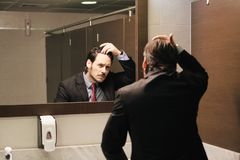 Worried Hispanic Business Man Looking At Hairline In Office Restrooms. Business man in office bathroom. Stressed manager using restrooms, washroom and lavatories royalty free stock photography