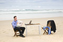 Business man with office on the beach Stock Photography